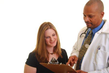 Afrikaanse Amerikaanse mannelijke arts weer gegeven een caucasian vrouw iets op een klembord.