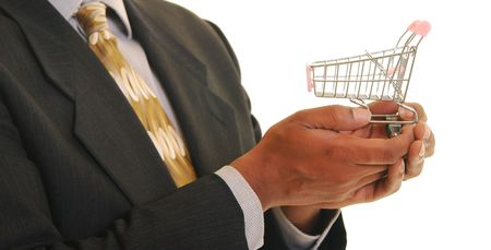 African american male holding a miniature shopping cart off to one side. Shallow depth of field. Focus on hands and shopping cart.
