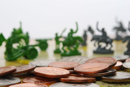 Figures of war out of focus behind a pile of U.S. coinage.