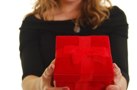 Caucasian woman giving a red gift. Shallow depth of field. Focus on present. Stock Photo