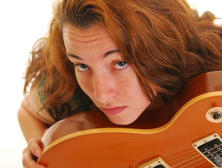 Beautiful caucasian woman resting her chin on side of a guitar.