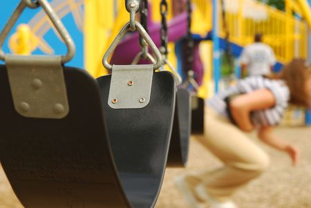 a close up of an empty swing at the playground, focus on swing, shallow depth of field.  Stock Photo