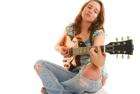 Woman sitting Indian style playing a guitar, isolated on white. Stock Photo