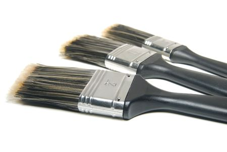 Three paint brushes of different sizes over white