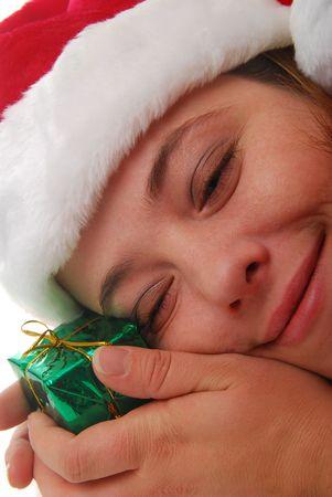 smiling woman wearing Santa hat holding gift