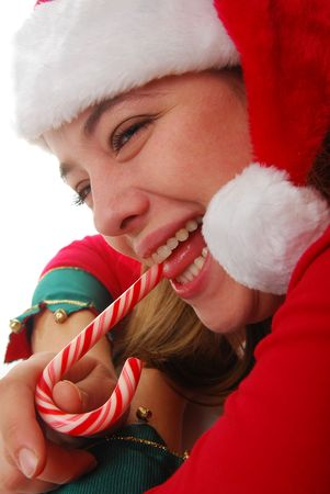 woman Santa eating candy cane isolated on white.  Stock Photo