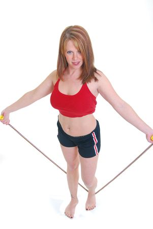 middle aged woman jump roping isolated on white.