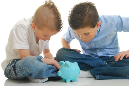 two young boys staring at piggy bank isolated on white.
