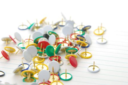 pin board: assortment of colored tacks laying on paper Stock Photo