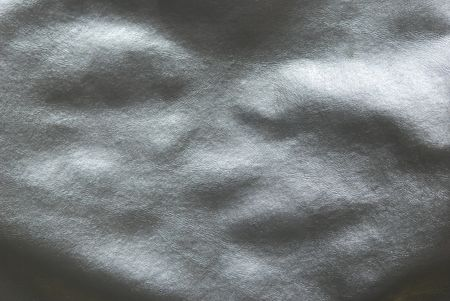 close up of black leather fabric with lumpy texture.