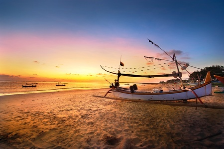 Drifting boat on the beach at sunset time . Bali , Indonesia