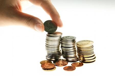 Concepto de educación financiera con mano poniendo muchas monedas