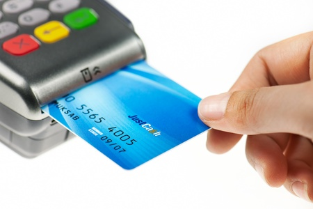 card payment: Close-up of  hand putting credit card into payment machine .