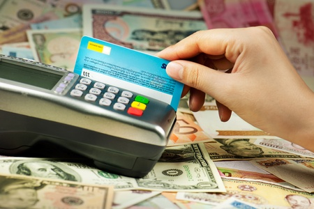 spending: Close-up of human hand putting credit card into payment machine
