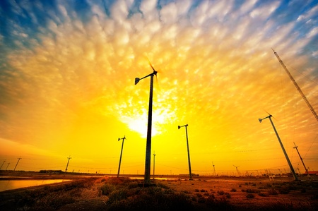 Wind turbines during beautiful sunset . There are new energy of Thailand. photo