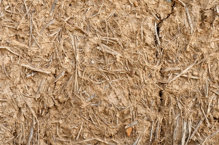 Old cracked wall made of orange clay and straw photo