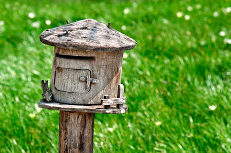Wooden mailbox. In the middle of green pastures.