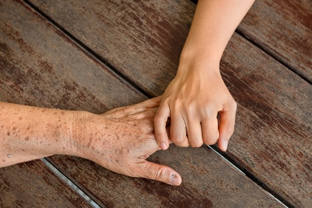 mature old generation: old and young woman hands touching