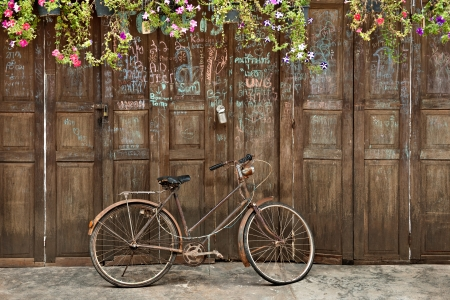 old style rusty brown bicycle and wood door