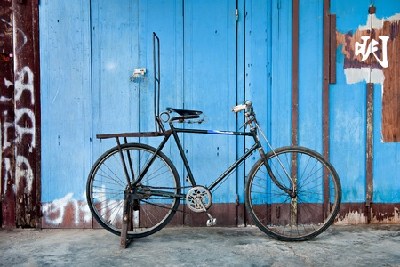 old style rusty  bicycle and blue wood door Stock Photo