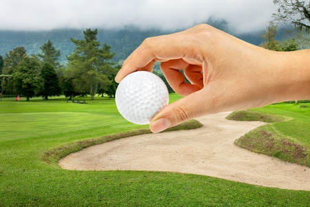 Hand holding ball in Golf course on the hill at Bali , Indonesia photo