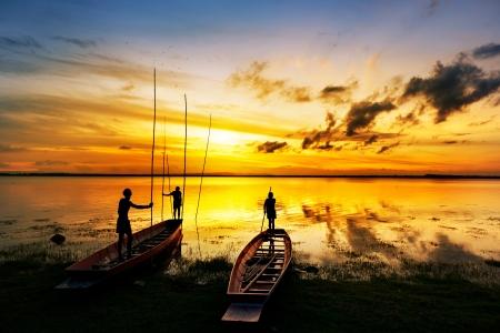 the boat on the river: silueta de los ni�os en el barco de madera al atardecer