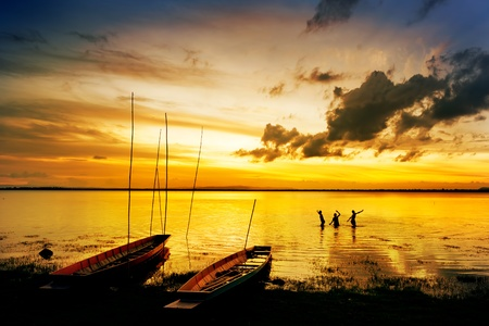 silhouette of children on wood boat at sunset photo