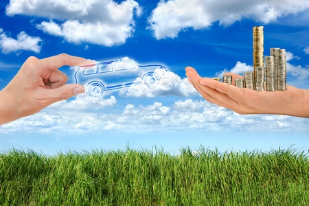 Hand holding car and money in green grass blue sky  photo