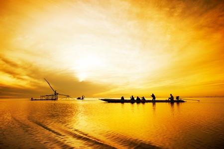 tourist travelling fisherman fishing at sunrise , thailand photo