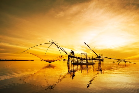 fisherman get fishing nets from river photo