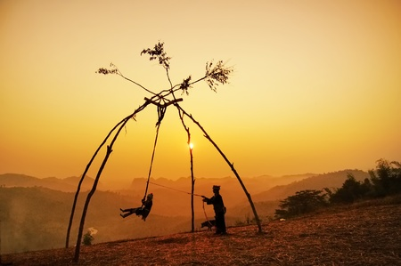silhouette of minority in thailand play swings Stock Photo