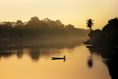 Silhouette of a fisherman in a boat on a river in the morning  photo