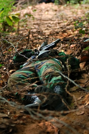 special operations: soldier carrying m16 crawling under barb  in combat training