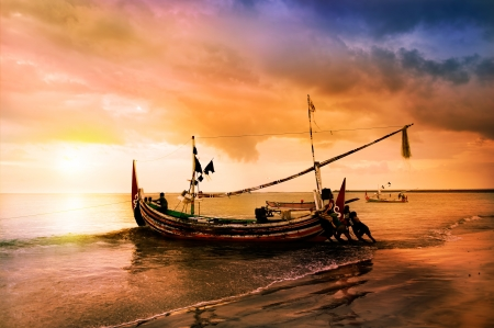 local boat on the beach at sunset time . Bali , Indonesia
