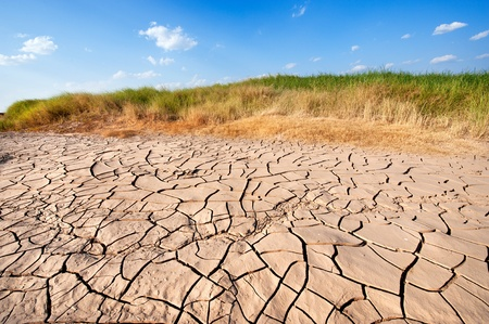 The dry earth and blue sky  after the water level in the river decreased in thailand photo