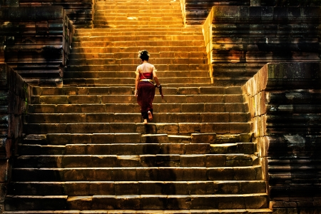 girl climbing up stairs of castle stone Stock Photo