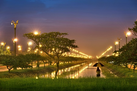 street lamps: girl carry umbrella in perspective canal Stock Photo