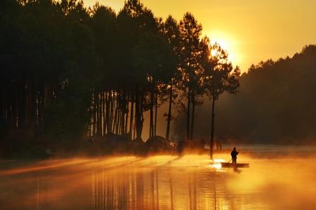 hobby hut: Fisherman in sunrise background  Stock Photo