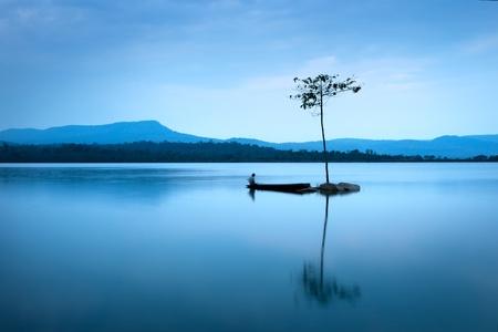 Fisherman in  fishing boat at big lake on the mountain photo