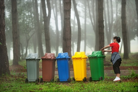 trash basket: cinco colores papeleras de reciclaje en el bosque de pinos Foto de archivo