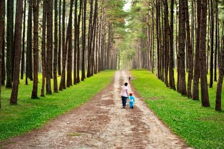 Madre e bambino a piedi sulla strada di campagna rurale in pineta