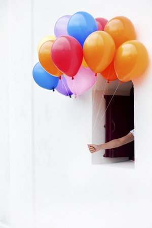 hand holding color balloons  from window photo