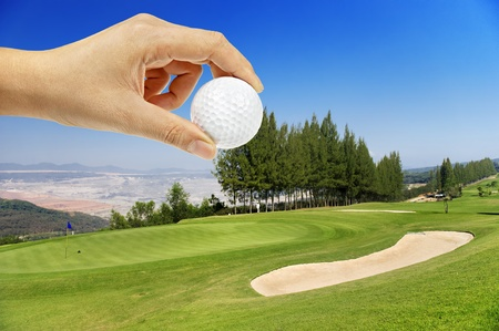 Hand holding golfball in golf course on hill photo