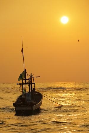 Old Fisherman boat at sunrise photo
