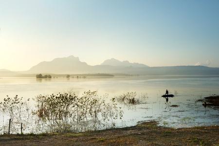 fisherman fishing in big lake ,thailand photo