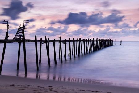 Old wood bridge to sea photo