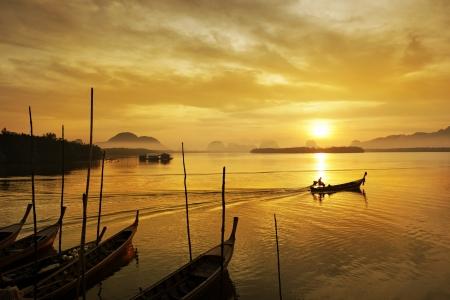 fisherman boat: Fisherman paddle boat in sunrise