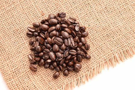 cyst: Fresh coffee beans in hemp sack on white background,Selective focus with shallow depth of field. Stock Photo