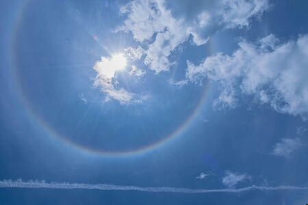 The silhouette sun halo at noon with the blue sky cloud, the beam, light and lens flare effect tone background. 스톡 콘텐츠