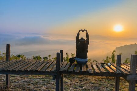 Silhouette the sunrise with a wooden skywalk, the fog, the beautiful sky and cloud at Phu Lam Duan Mountain, Pak Chom District, Loei Province, Thailand. Stock Photo
